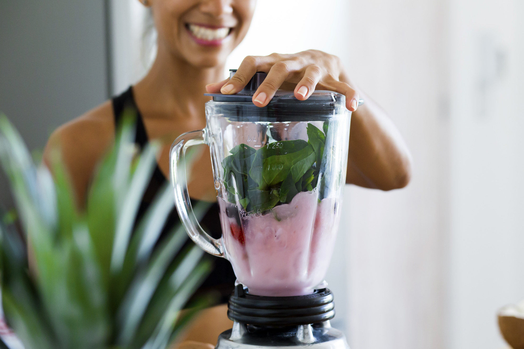 woman blending spinach, berries, and almond milk smoothie
