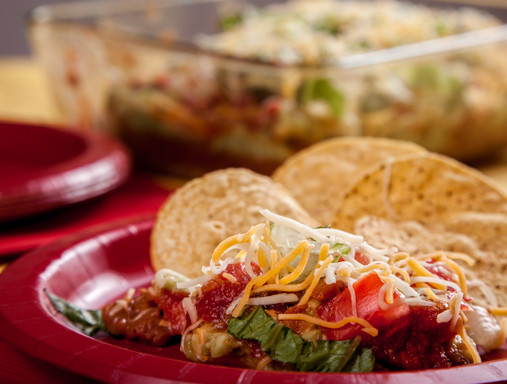 chips and taco dip on a red plate
