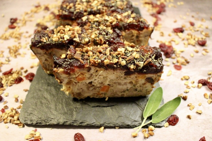 turkey meatloaf topped with nuts and cranberries on slate board